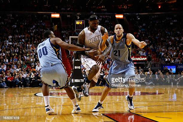 LeBron James of the Miami Heat drives against Tayshaun Prince of the Memphis Grizzlies and Darrell Arthur of the Memphis Grizzlies at American...