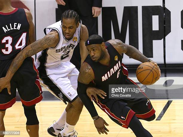 LeBron James of the Miami Heat drives around Kawhi Leonard of the San Antonio Spurs in Game Five of the 2014 NBA Finals at the ATT Center on June 15...