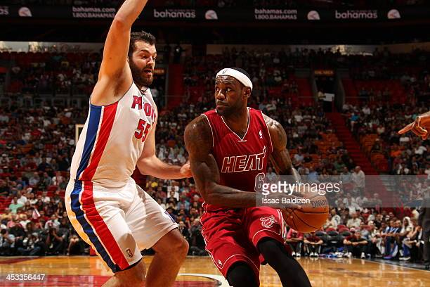 LeBron James of the Miami Heat drives to the basket against Josh Harrellson of the Detroit Pistons on December 3 2013 at American Airlines Arena in...