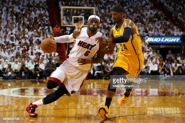LeBron James of the Miami Heat drives to the basket against Paul George of the Indiana Pacers in the first period during Game Three of the Eastern...