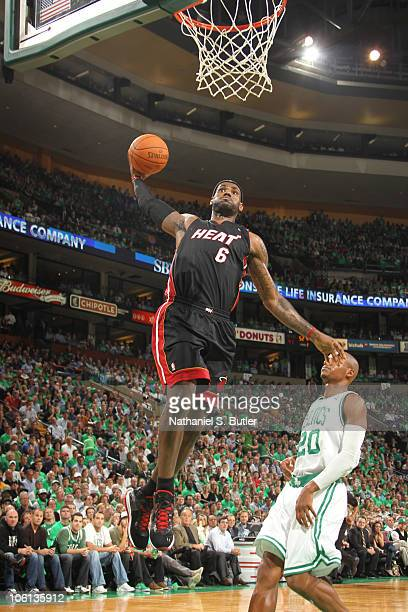 LeBron James of the Miami Heat dunks against Ray Allen of the Boston Celtics during a game on October 26 2010 at TD Garden in Boston Massachusetts...