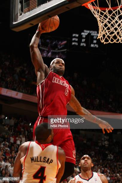 LeBron James of the Miami Heat dunks the ball against Paul Millsap of the Atlanta Hawks on December 23 2013 at American Airlines Arena in Miami...
