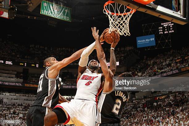 LeBron James of the Miami Heat goes to the basket against Tim Duncan and Kawhi Leonard of the San Antonio Spurs during Game Seven of the 2013 NBA...