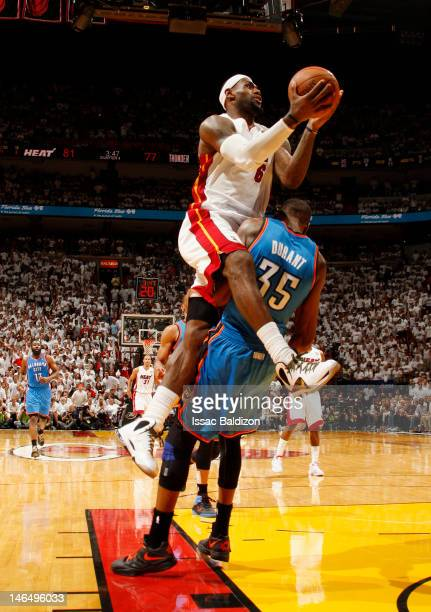 LeBron James of the Miami Heat goes to the basket as Kevin Durant of the Oklahoma City Thunder gets called for a blocking foul during Game Three of...