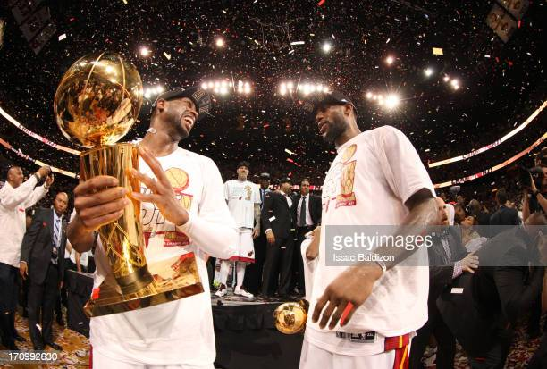 LeBron James of the Miami Heat holds his Bill Russell NBA Finals Most Valuable Player Award; Dwyane Wade of the Miami Heat holds the Larry O'Brien...