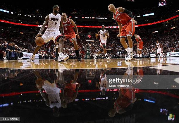 Lebron James of the Miami Heat is guarded by Corey Maggette and Drew Gooden of the Milwaukee Bucks during a game at American Airlines Arena on April...