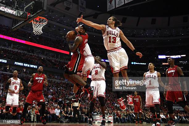 LeBron James of the Miami Heat is on the receiving end of a flagrant foul by Carlos Boozer of the Chicago Bulls as Joakim Noah of the Bulls also...