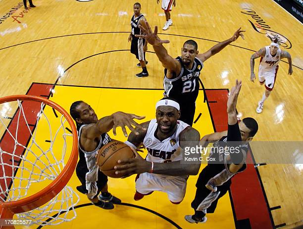 LeBron James of the Miami Heat looks to go up for a shot against Kawhi Leonard Tim Duncan and Danny Green of the San Antonio Spurs in the first half...