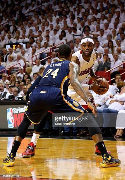 LeBron James of the Miami Heat looks to pass as Paul George of the Indiana Pacers defends during Game Four of the Eastern Conference Finals of the...