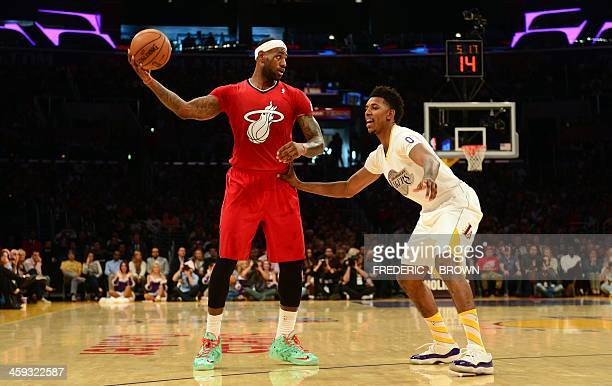 Lebron James of the Miami Heat looks to pass under pressure from Nick Young of the Los Angeles Lakers during their Christmas Day matchup at Staples...