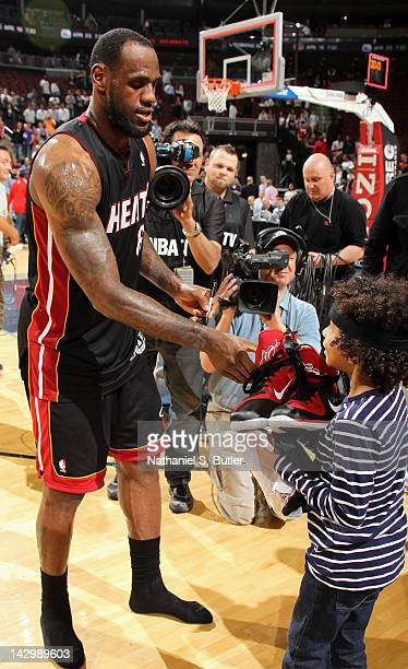 LeBron James of the Miami Heat presents a young fan with the sneakers he wore during the game against the New Jersey Nets on April 16 2012 at the...