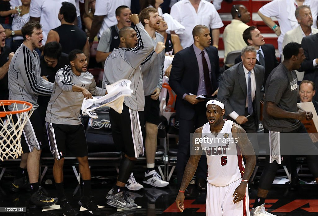LeBron James #6 of the Miami Heat reacts as the San Antonio Spurs bench cheers after Tony Parker #9 (not seen) makes a shot with 5.2 seconds remaining in the fourth quarter during Game One of the 2013 NBA Finals at AmericanAirlines Arena on June 6, 2013 in Miami, Florida.