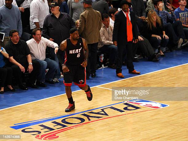 sports shoes f0a6c a4bbe LeBron James of the Miami Heat runs past director Spike Lee after James  made a 3point