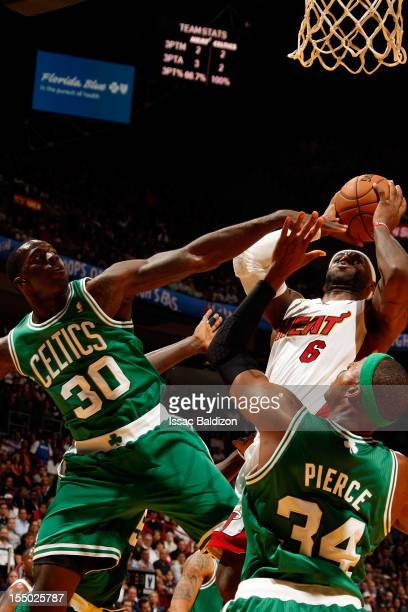 LeBron James of the Miami Heat shoots against Brandon Bass and Paul Pierce of the Boston Celtics during the NBA game on October 30 2012 at American...