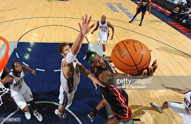 LeBron James of the Miami Heat shoots against Brook Lopez of the New Jersey Nets on April 3 2011 at the Prudential Center in Newark New Jersey NOTE...