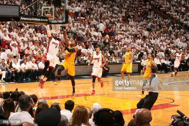 LeBron James of the Miami Heat shoots against Paul George of the Indiana Pacers in Game Six of the Eastern Conference Finals during the 2014 NBA...