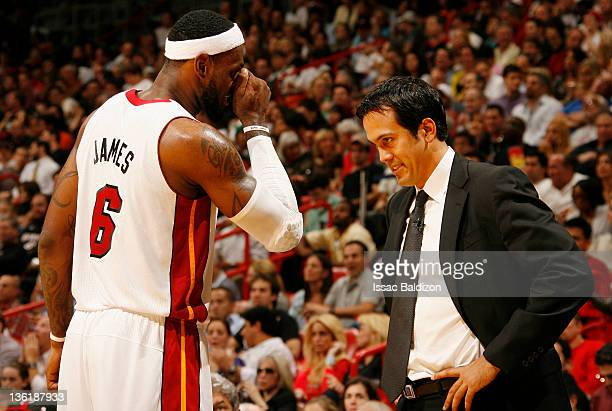 LeBron James of the Miami Heat talks to head coach Erik Spoelstra during the first half of the home opener against the Boston Celtics on December 27...