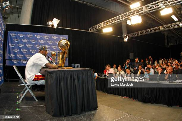 LeBron James of the Miami Heat talks to the media while displaying both the Larry O'Brien NBA Championship Trophy and the Bill Russell Finals MVP...