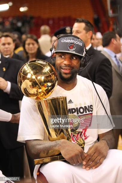 LeBron James of the Miami Heat talks to the media while holding the Larry O'Brien NBA Championship Trophy after his team wins the NBA Championship by...