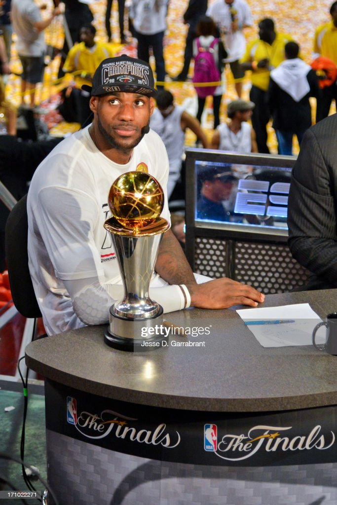 LeBron James #6 of the Miami Heat waits to be interviewed while sitting with the Bill Russell NBA Finals Most Valuable Player (MVP) trophy following the Heat's victory against the San Antonio Spurs in Game Seven of the 2013 NBA Finals on June 20, 2013 at American Airlines Arena in Miami, Florida.