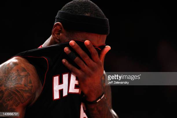 LeBron James of the Miami Heat wipes his face with his jersey in the first half against the New York Knicks in Game Four of the Eastern Conference...