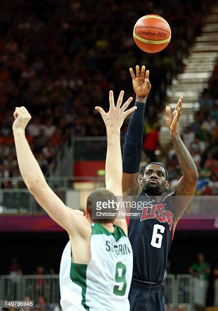 Lebron James of United States puts up a three point shot over Darius Songaila of Lithuania during the Men's Basketball Preliminary Round match on Day...