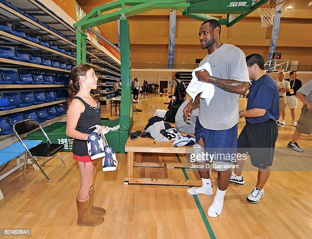 LeBron James of US Men's Senior National Team gives his sneakers to a young girl who found her way into practice during the 2008 Beijing Summer...