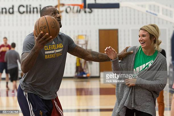 LeBron James playfully pushes Allie Clifton out of his way as he shoots Clifton works for a company which is a partner to the Cavs organization...