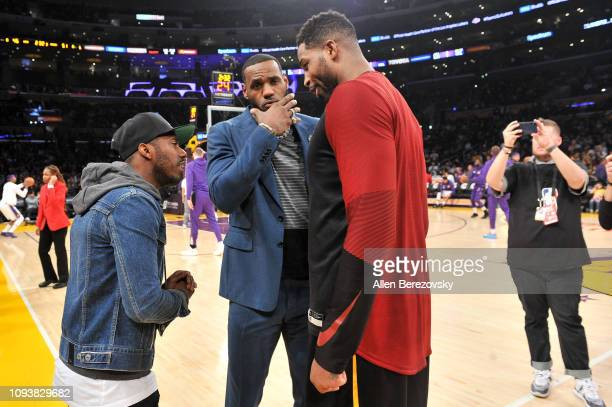 LeBron James talks to his agent Rich Paul and his former teammate Tristan Thompson during halftime of a basketball game between the Los Angeles...