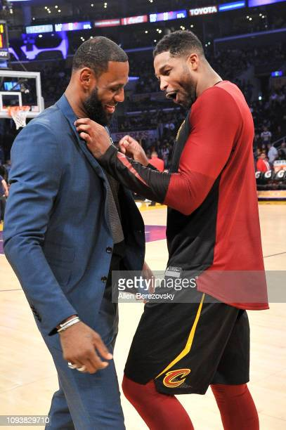 LeBron James talks to his former teammate Tristan Thompson during halftime of a basketball game between the Los Angeles Lakers and the Cleveland...