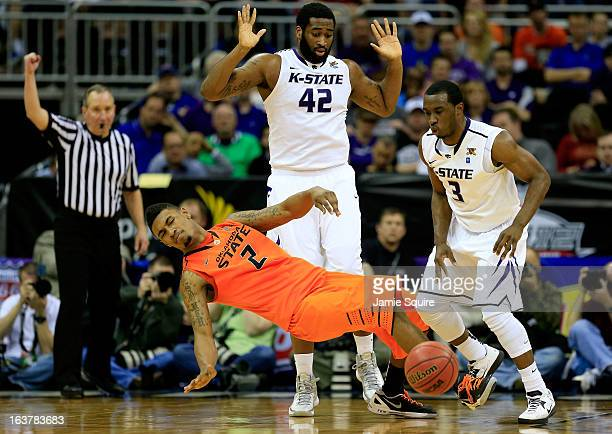 Le'Bryan Nash of the Oklahoma State Cowboys falls after getting hit in the face by Thomas Gipson of the Kansas State Wildcats as Martavious Irving...