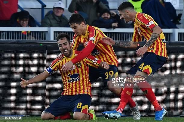 Lecce's Italian midfielder Marco Mancosu celebrates with Lecce's Italian defender Cristian Dell'Orco and Lecce's Italian midfielder Alessandro Deiola...