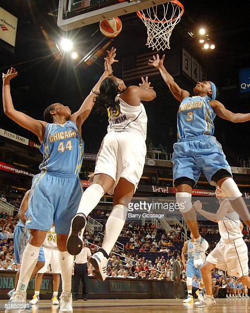 Le'coe Willingham of the Phoenix Mercury shoots against Chasity Melvin and Dominique Canty of the Chicago Sky on June 20 at U.S. Airways Center in...