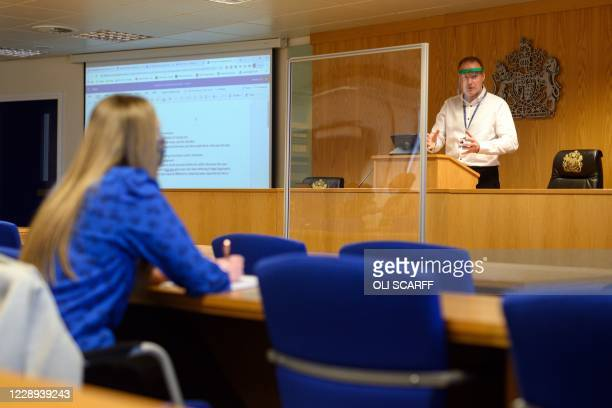 Lecturer Ian Bowden teaches law students wearing face coverings to help mitigate the spread of the novel coronavirus COVID-19, from behind a perspex...