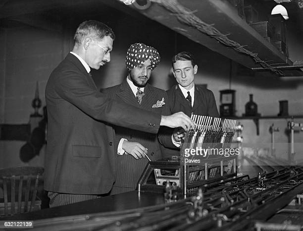 Lecturer Mr Holmes demonstrating a railway signalling mechanism to an Indian student and a junior employee in a free educational class provided for...
