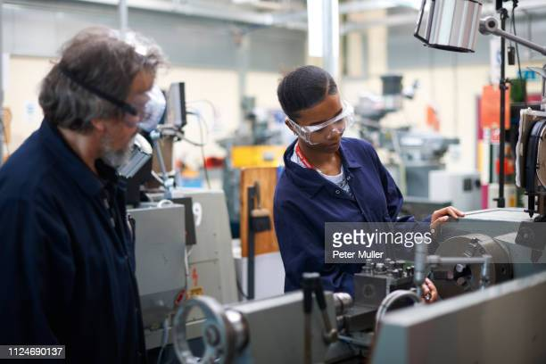 lecturer teaching student to operate machine in workshop - demonstration stock pictures, royalty-free photos & images