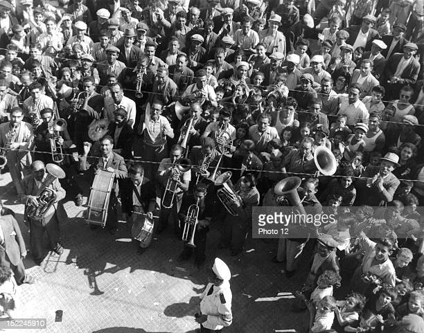 Led by a brass band enthusiastic civilians of a Sicilian town cheer the welcome news about the Armistice between the Allies and Italy