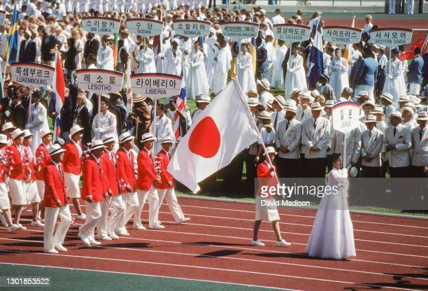 Led by flagbearer Mikako Kotani, the team from Japan marches in the Parade of Athletes during the Opening Ceremony of the 1988 Olympic Games on...