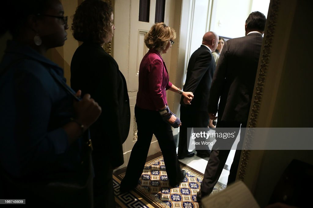 Led by her husband Mark Kelly, former U.S. Rep. Gabrielle Giffords (D-AZ) (C) arrives at the weekly Senate Democratic Policy Luncheon April 16, 2013 on Capitol Hill in Washington, DC. Giffords was on the Hill to discuss gun control with Sen. Joe Manchin (D-WV) and Sen. Pat Toomey (R-PA).