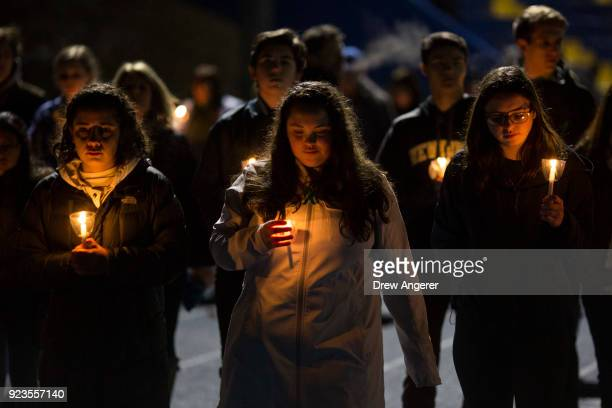 Led by high school students mourners walk around the track of the football field with candles during a community vigil at Newtown High School for the...