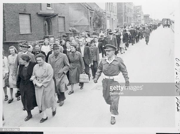 Led by the city's burgomeister and Captain A Stirling the District Assistant Provost Marshal citizens of Burgsteinfurt Germany march to the theater...