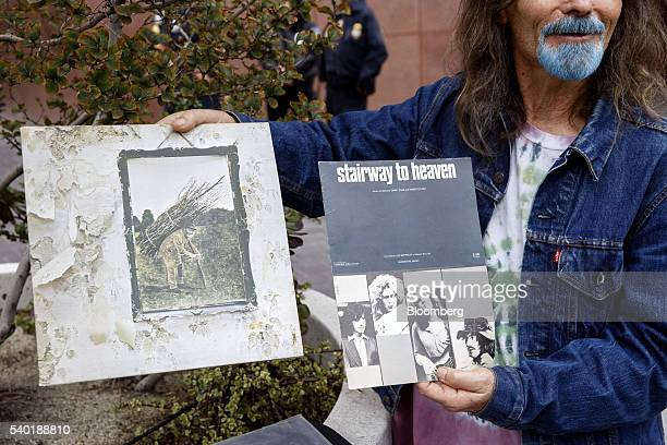 A Led Zeppelin fan holds up an album and sheet music for Stairway to Heaven outside of federal court in Los Angeles California US on Tuesday June 14...