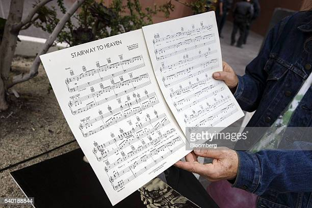 A Led Zeppelin fan holds up sheet music for Stairway to Heaven outside of federal court in Los Angeles California US on Tuesday June 14 2016 Jimmy...