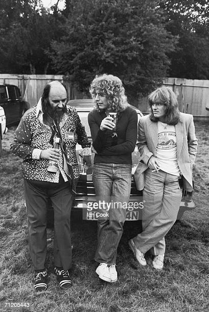 Led Zeppelin manager Peter Grant leans on the hood of a car with the band's singer Robert Plant and bassist John Paul Jones at the Knebworth Music...