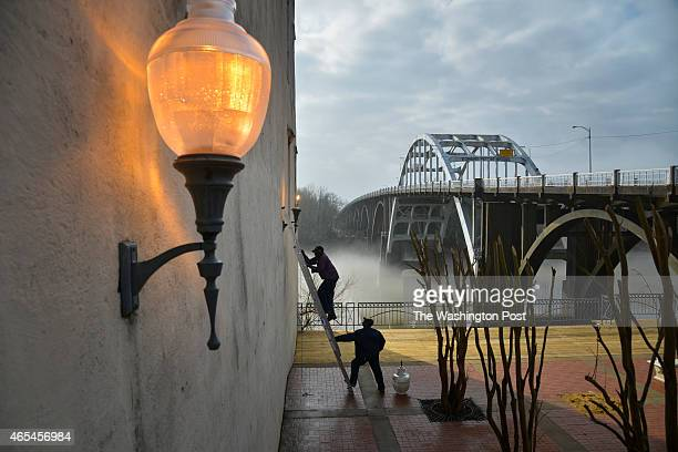 Ledell Tenner on ladder and Frank Murry both electricians with the city of Selma change lights and their fixtures at the foot of the historic Edmund...