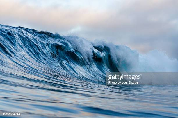 a ledgy wave breaking over shallow reef - twilight stock pictures, royalty-free photos & images