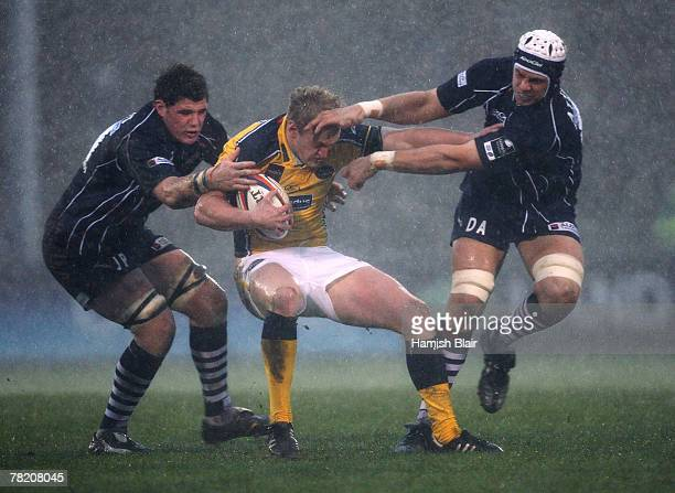 Lee Blackett of Leeds is tackled by James Phillips and Dave Attwood of Bristol during the EDF Energy Cup match between Bristol Rugby and Leeds...