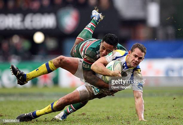 Lee Byrne of Clermont Auvergne is tackled by Manu Tuilagi during the Heineken Cup match between Leicester Tigers and Clermont Auvergne at Welford...