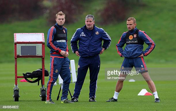 Lee Cattermole and Seb Larsson chat with assistant manager Paul Bracewell during a Sunderland training session at the Academy of Light on October 30...