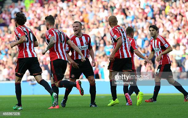 Lee Cattermole of Sunderland celebrates with teammates after Harry Kane of Tottenham scored an own goal to bring the scores level at 2-2 during the...